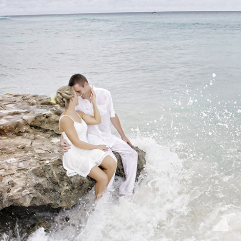 Photo of bride and groom sitting on rock with feet in ocean.