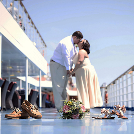 Photo of bride and groom kissing on ship deck with shoes and flowers in focus in the foreground.