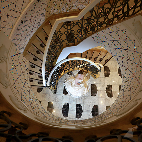 Photo of bride standing at bottom of spiral staircase taken from above.