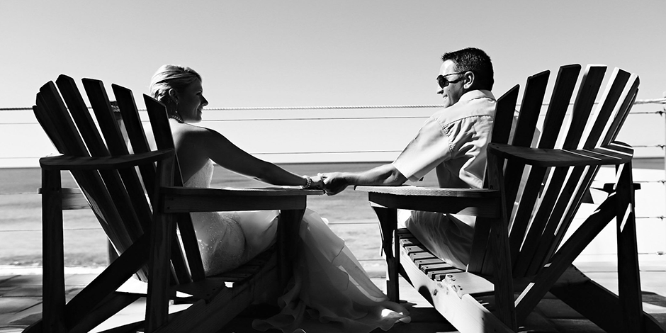 Black and white photo of bride and groom holding hands as they sit in chairs overlooking the ocean.
