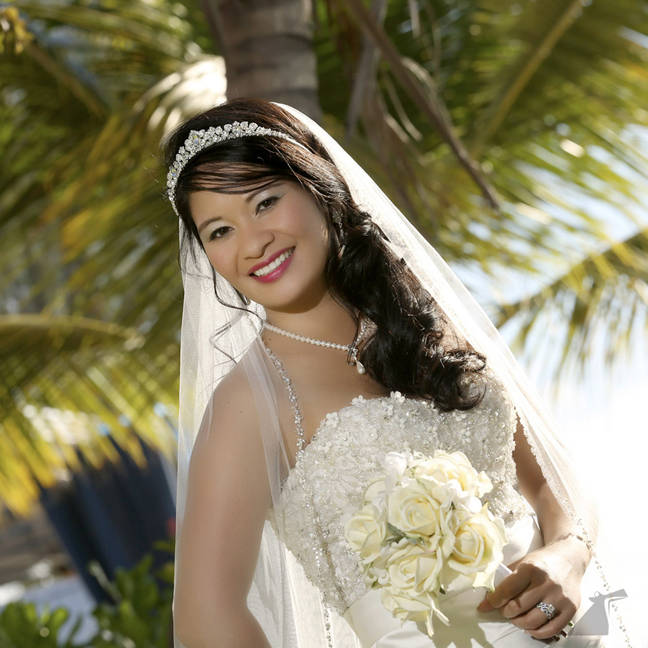 Photo of bride holding flowers in front of palm tree.