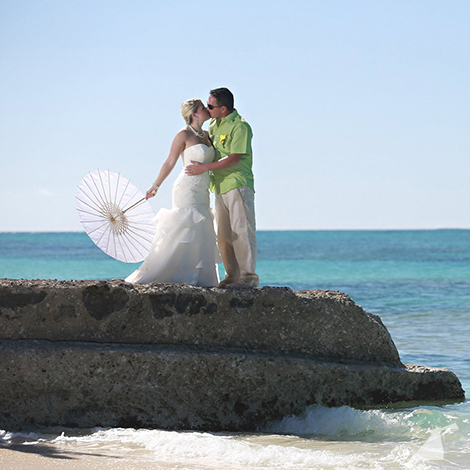 Photo of bride and groom kissing on rock in the ocean.