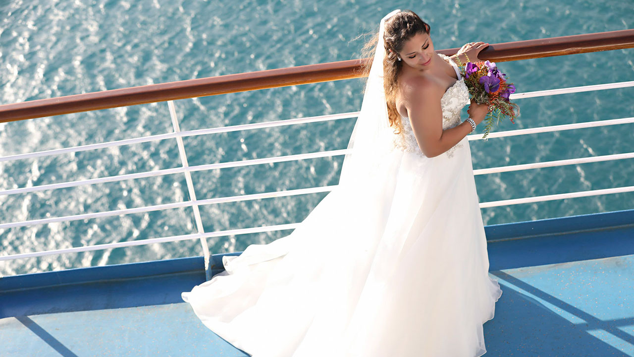 Photo of bride holding flowers on ship deck and ocean in background, taken from above.