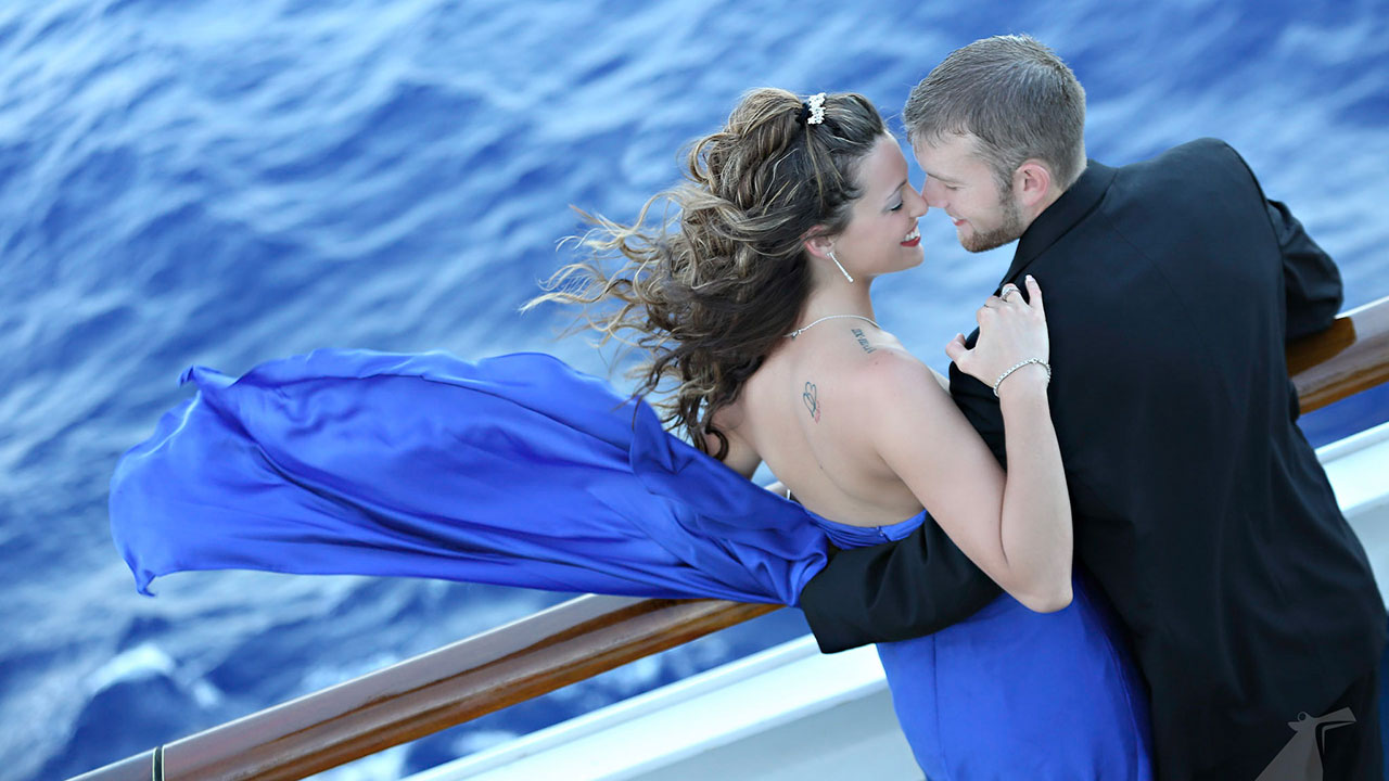 Photo from above of bride and groom embracing on ship deck with ocean in background.