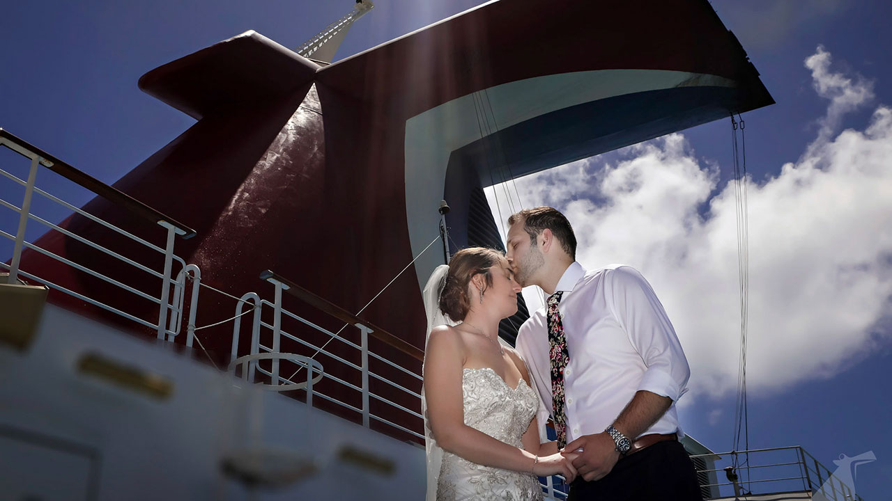 Low-angle photo of bride and groom embracing on ship deck with Carnival funnel in background.